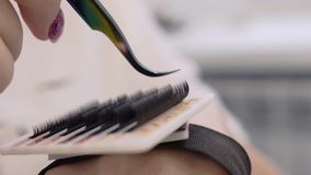 Stylist in the beauty salon holds a special tool for sets of false eyelashes. Very close-up of beautiful devices. And parts in the beauty salon stock video
