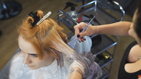 Stylist Beauty Studio causes the paint to hair to locks of blonde. In the client chair young nice girl stock video