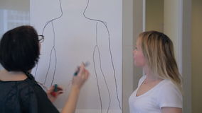 Stylist begins to work on silhouette of client, circled on large sheet of paper. stock video footage