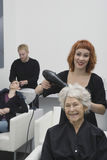 Stylist Blow Drying Senior Woman's Hair In Salon. Happy female stylist blow drying senior woman's hair in salon Royalty Free Stock Image