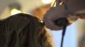 Stylist curling hair for young woman stock video