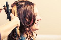 Stylist curling hair for young woman. Stock Images