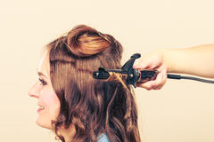 Stylist curling hair for young woman. Royalty Free Stock Images