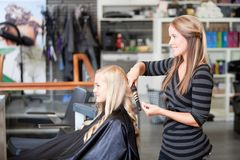 Stylist Curling Womans Hair Stock Photo