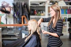 Stylist Curling Womans Hair. In beauty salon Stock Photo