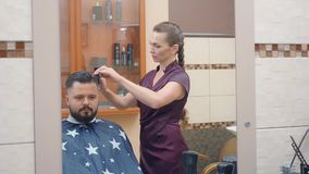Stylist cutting males hair with scissor and comb, medium shot. Master and client reflecting in mirror, recorded in. Barbershop. Selective soft focus. Blurred stock footage