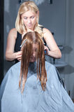 Stylist cutting woman hair in salon Stock Photography
