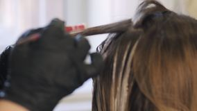 Stylist does hair coloring in beauty studio, woman changes her look, professional coloring and hair care, beauty stock footage