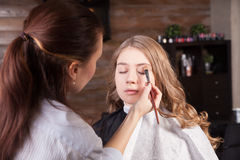 Stylist doing professional make up of young woman Stock Image