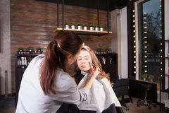 Stylist doing professional make up of young woman Royalty Free Stock Images