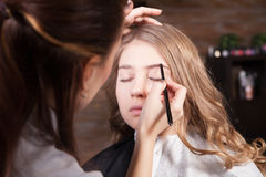 Stylist doing professional make up of young woman Stock Photo
