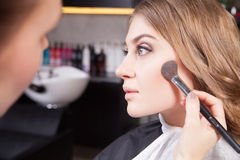 Stylist doing professional make up of young woman Stock Photos