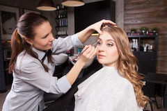 Stylist doing professional make up of young woman Stock Images