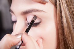 Stylist doing professional makeup of young woman Stock Photography