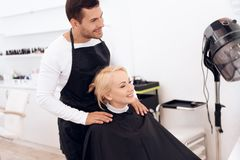 Stylist dresses hairdressing collar on mature woman`s neck. Female haircut. royalty free stock photography