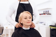Stylist dresses hairdressing collar on mature woman`s neck. Female haircut. royalty free stock images