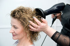 Stylist drying woman hair. In hairdresser salon Stock Image