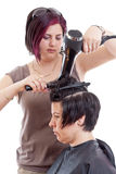 Stylist drying woman hair. Stylist drying women hair, isolated on white Royalty Free Stock Image