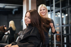 Stylist drying woman hair in beauty salon. Young stylist drying women hair in beauty salon Royalty Free Stock Photography