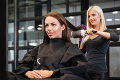 Stylist drying woman hair in beauty salon. Young stylist drying women hair in beauty salon Stock Photography