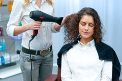 Stylist drying woman hair in salon Stock Photography