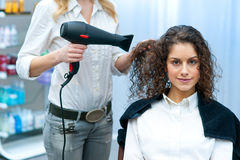 Stylist drying woman hair in salon Royalty Free Stock Photos