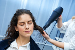 Stylist drying woman hair in salon Stock Image