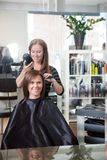 Stylist Drying Woman's Hair Stock Images