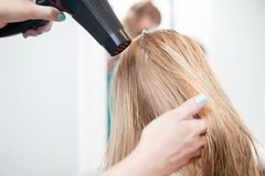 Stylist Drying Womans Hair Stock Photo