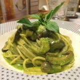 Stylist food, Close up Italian pasta spaghetti homemade green pesto sauce, mushroom top with basil leaf on white plate with blur r stock photo