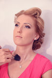 Stylist geting make-up on a woman Royalty Free Stock Photos