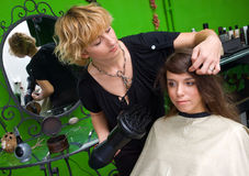 Stylist with hair dryer working. Stylist with dryer working on woman hair royalty free stock photos