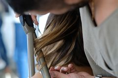 Closeup hairdresser coiffeur makes hairstyle. Stylist hairdresser doing haircut closeup of work equipment, the beauty industry.Wedding royalty free stock photo