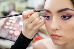 Stylist hand doing professional eyebrow makeup with brush. Beautiful model Royalty Free Stock Photos
