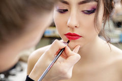 Stylist hand doing professional lips makeup with brush. Red lips. Beautiful model. Isolated on white background Stock Photos