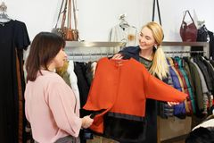 Stylist helping chooses clothes for the customer Royalty Free Stock Image
