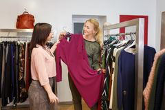 Stylist helping chooses dress for the customer. Sales consultant helping chooses dress for the customer in the store. Shopping with stylist. Beautiful female Stock Images