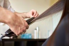 Stylist with iron straightening hair at salon Stock Photo
