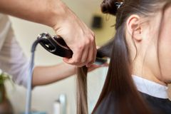 Stylist with iron straightening hair at salon Royalty Free Stock Photos