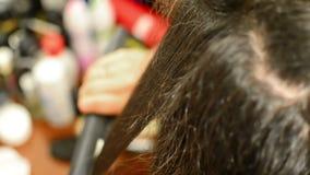 Stylist ironing long hair Royalty Free Stock Photos
