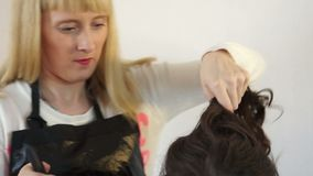 Stylist looks at the head of the model. And puts her hair stock video
