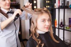 Stylist make curls hair in salon. Portrait of stylist making curls hair in salon stock photos