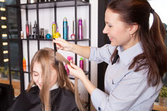 Stylist make curls hair in salon Royalty Free Stock Images