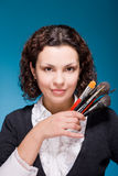 Stylist with make up brushes on blue Stock Image