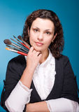 Stylist with make up brushes on blue Royalty Free Stock Image