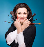 Stylist with make up brushes on blue background Stock Photography