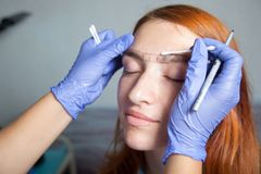 Stylist makes eyebrow. A close-up of the beautician, the stylist makes eyebrow correction and draws the correct shape of the eyebrows in blue medical gloves red royalty free stock photography