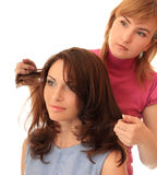 Stylist makes hair. Beautiful girl royalty free stock images
