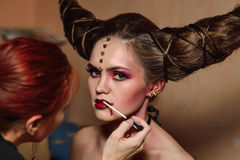 Stylist makes halloween makeup, brushing blood on models lips.  stock photography