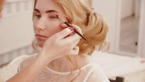 Stylist makes eyes makeup to the blonde bride girl stock video footage